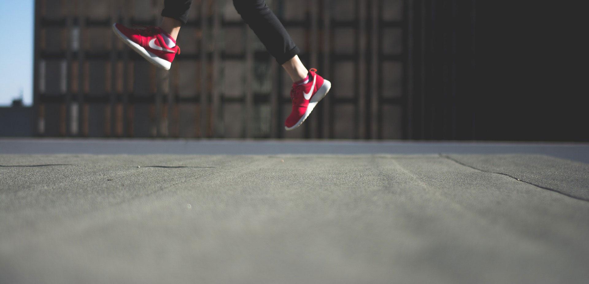 Frau hüpft mit roten Turnschuhen